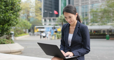 Adult student works on laptop, outside, during a workbreak; dressed professionally
