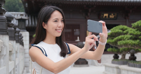 Travel woman use of smart phone to take phone and video in Chinese garden