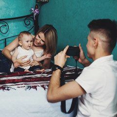 Family photo. Man taking pictures of woman and little girl. Dad making portrait of mom and daughter on modern camera. Photography, blogging, parenting, childhood concept