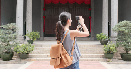 Woman holding camera to take video and walk into chinese temple