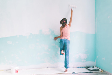 Child painting a wall in room