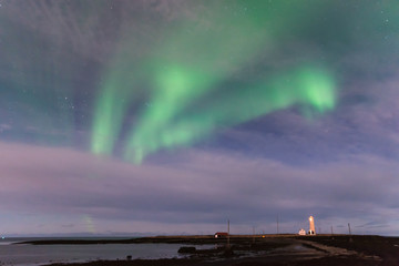 Green Aurora Borealis over the Grotta Lighthouse in Iceland with the ocean and a black sand beach in the foreground