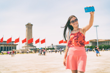 Asian woman taking selfie photo with phone in Beijing, China. Asia travel. Tourist girl sightseeing famous sight holding mobile smartphone visiting Tiananmen Square. Summer vacation.