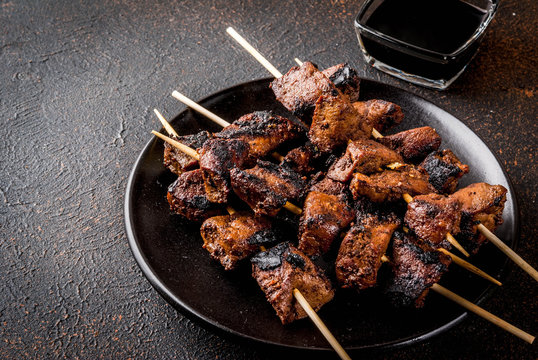 Grilled beef liver on skewers, with teriyaki or soy sauce, yakitori, dark rusty  table copy space top view