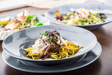 Pasta linguine with confit duck breast parmesan cheese and herb decoration