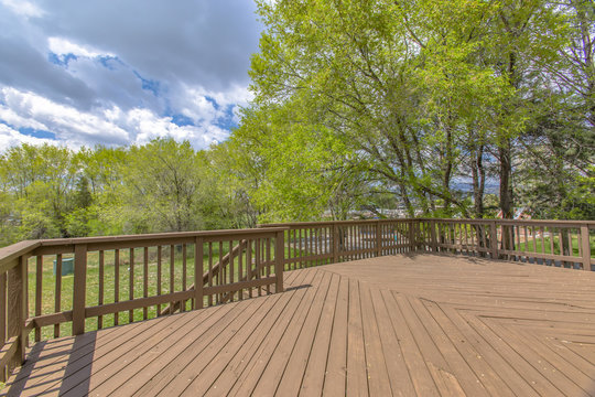 Wooden deck with cloudy skies and green trees