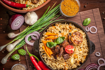 The concept of eastern, Uzbek cuisine. Pilaf, plov in a black cast-iron frying pan on a wooden table, next to lie ingredients, onions, tomatoes, parsley, pepper. Central Asian cuisine. Top view