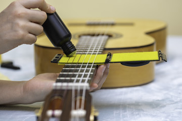 Care and maintenance of the strings of a guitar.