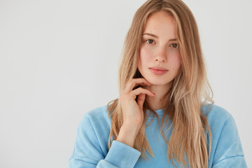 Photo of pretty female has serious look at camera, long hair, dressed in blue sweater, has gentle smile, shows her natural beauty, poses against white background with copy space for advertisement