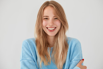 Portrait of happy attractive European female with folded arms, gentle sincere smile, being in great mood, spends spare time with boyfriend who tells funny stories, isolated over white background
