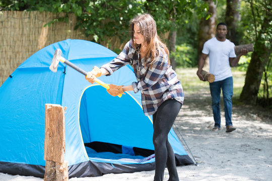 Woman chopping wood as man carrys logs while camping