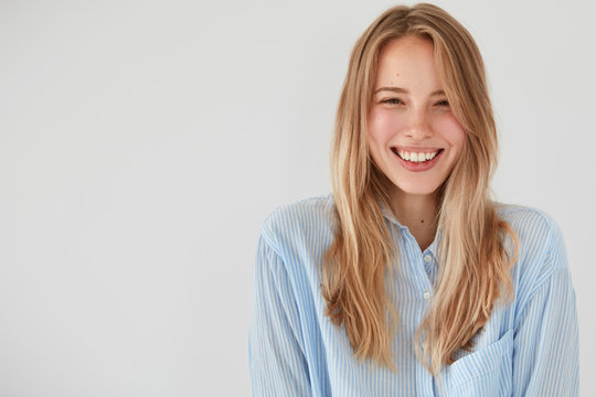 Joyful pretty young woman giggles positively at camera, dressed in casual shirt, shows beauty, poses against white background with blank copy space for your advertisement or promotional text