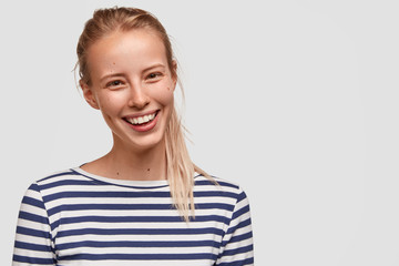 Portrait of postive glad adorable female student with pony tail, dressed in casual striped sweater, has broad smile, stands against white background, happy to recieve good mark for project work