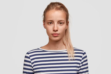 Close up portrait of beautiful female trainer in casual striped t shirt, waits for new group for training, has combed hair, pure skin, looks directly at camera, isolated over white background