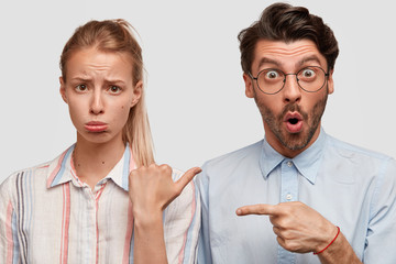 Wall Mural - Unhappy female points at shocked hipster guy, indicate at each other, isolated om white studio background. Surprised unshaven stylish man in spectacles stands near his displeased girlfriend.