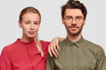 Wall Mural - Isolated shot of family couple stand close to each other, wears elegant clothes, look seriously, confident they will become parents very soon. Shot of beautiful girl leans at shoulder of husband
