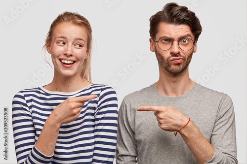 Wall mural Horizontal shot of two female and male best friends express different emotions, pose together against white blank wall. Cheerful young woman and puzzled unshaven male indicate at each other.