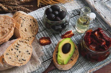 Homemade bread with olives with sun-dried tomatoes, avocado and olive oil