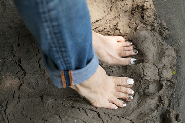 Bare feet in muddy sand