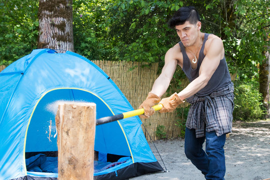 Strong hispanic man splitting wood for fire on camping trip near tent