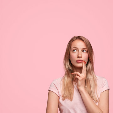 Vertical shot of thoughtful European female looks upwards, keeps fingers on cheek, contemplates about future wedding with boyfriend, dressed casually, has weekend, isolated on pink wall. Monochrome