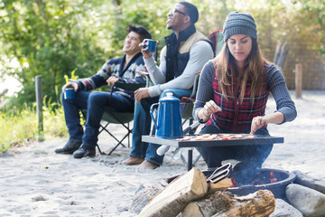 Woman cooking bacon over an open fire while camping