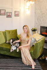 Young caucasian woman wearing dress sitting on sofa in living room with husky. Concept of pets, celebrating holidays, fashion and interior.