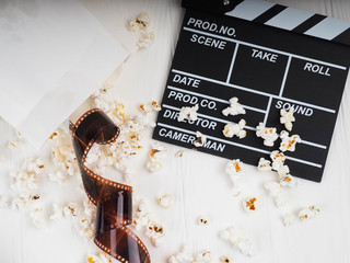 the film in the spiral, near the popcorn, Clapperboard copy space for text, fashion highlights in the photo, concept, film industry, film, abstract composition of movie, on a white background