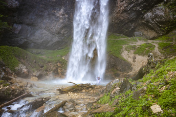 European man with beard is doing waterfall-meditation while standing under big waterfall in austria, wildensteiner waterfall