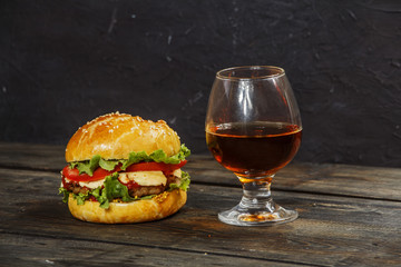Hamburger on a wooden board against a dark background with copy space. Hamburger with sauce and fresh vegetables on a wooden table. Burger.
