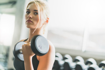 attractive caucasian woman workout with dumbbells exercises in gym fit and firm concept