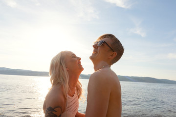 Happy couple in love laughing at the beach against sun
