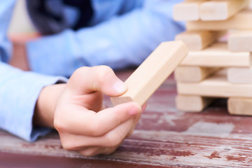 Close up kid's hand playing wood blocks tower game for practicing physical and mental skill.