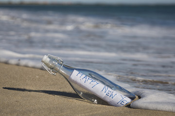 A Happy New Year Message in a bottle at the beach.