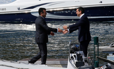 Greek Prime Minister Alexis Tsipras welcomes Macedonian Prime Minister Zoran Zaev before the signing of an accord to settle a long dispute over the former Yugoslav republic's name in the village of Psarades