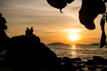 Lovers are sitting on the rocks watching the sunset at the beach.