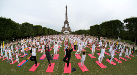 People gather for an open-air yoga session near the Eiffel tower in Paris