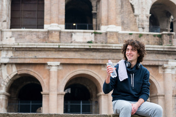 Handsome young sportsman holding water bottle and relaxing after training with a towel around his neck in front of Colosseum in Rome