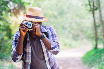 African man traveller take photo vintage camera film with green nature background.
