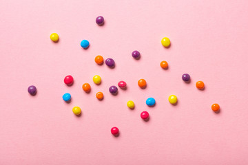 beautiful colorful glaze chocolate sprinkles on pink background, flat lay