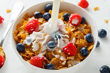 Healthy Morning Breakfast honey Corn flakes with fresh fruits of Raspberry, blueberries and pouring milk in bowl.
