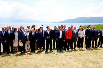 Macedonian Prime Minister Zoran Zaev and Greek Prime Minister Alexis Tsipras stand with delegations after the signing of an accord to settle a long dispute over name  of Republic of Macedonia arrived in the village of Otesevo