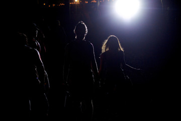 A couple is illuminated as they walk though emergency lights on the fourth and final day of the Firefly Music Festival in Dover, Delaware