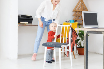 Smiling and joyful young mother plays with her baby boy two years old at home. Happy family spend time together. Motherhood and child