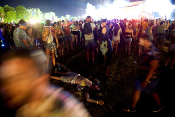 A reveler lies unresponsive during Martin Garrix performance at the Firefly Music Festival in Dover, Delaware