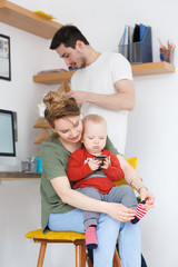 Everyday life of ordinary families. Young beautiful mother dresses socks to her small child playing smartphone against the backdrop of dad with magazine in modern interior