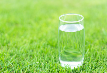 Closeup glass of water on green grass nature background, food healthy concept