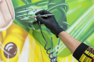 The artist paints a picture with a spray gun