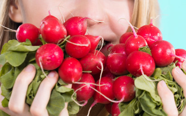 woman holding radish close to face