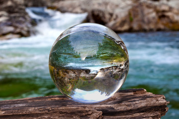 Crystal glass ball sphere reveals waterfall landscape with spherical perspective
